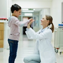 Female doctor and child paint giving high fives