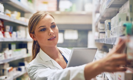 Young female pharmacist selecting medicine off a shelf