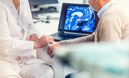 A doctor and his patient sitting at a table and looking at an MRI scan of the patient's brain which is showing a tumour.