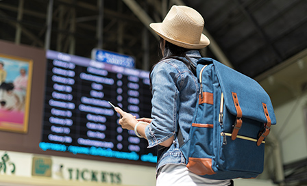 Backpacker young woman checking her train arrival in timetable board