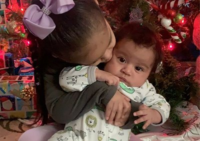 Jonathan's big sister gives him a sweet kiss in front of the Christmas tree.