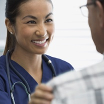 Female nurse smiling at a male patient