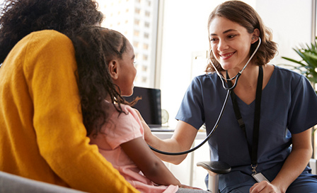 Female doctor using stethoscope to examine young girl while her mother holds her.