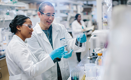 Two researchers in lab coats discussing a substance in a beaker.