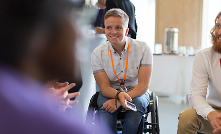 Smiling woman in wheelchair talking to colleagues in conference