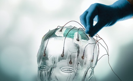Glass human head with sensors being placed on it.