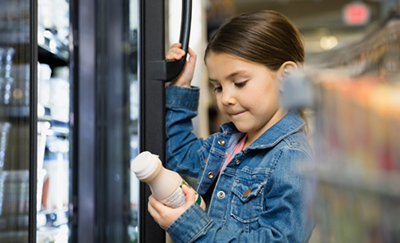 Young girl looking at a bottle of chocolate milk