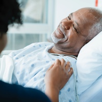 Man lying in hospital bed and smiling
