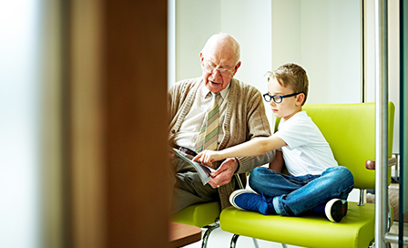 Indoors shot of little boy with his grandfather sitting in waiting room at dental clinic