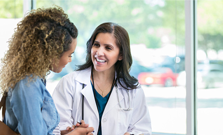 Caring mature female doctor shows test results to a young adult female patient. The doctor is smiling while talking with the patient.