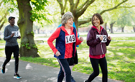 Active senior women friends power walking sports race in park